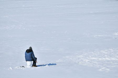 Ice fisherman sitting on a bucket above hole in the ice. Stock Photo - 6519314