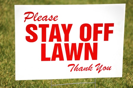 Red stay off the lawn sign on white background.