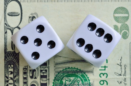 fifty dollar bill: Closeup of a pair of dice with eleven showing on a fifty dollar bill.