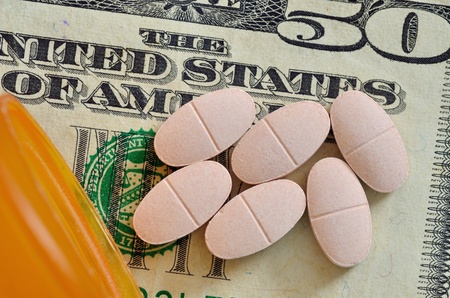 fifty dollar bill: A macro closeup of Prescription drugs on a fifty dollar bill.