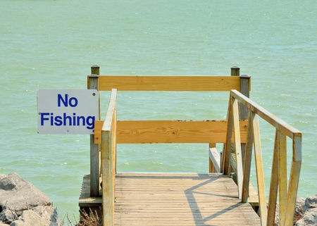 No Fishing sign on a dock on a lake.