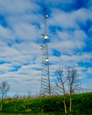 Telecommunication Tower against a cloudy blue  sky.