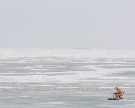 frozen lake: An ice fisherman on a frozen lake.
