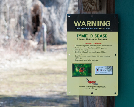 posted: Deer Tick Warning Sign posted in a nature park in New York State. Stock Photo