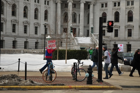 "restricting: Madison, Wisconsin, USA – 2-15-11 – Pedestrian carrying sign on grounds of the Wisconsin state capital that says ""Impeach Walker"" to protest the bill to balance the state budget by restricting collective bargaining rights for state union employees Editorial"