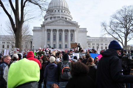 Madison, Wisconsin, USA – 2-15-11 – Large crowd of protesters, wielding signs on grounds of the Wisconsin state capital, who are there to protest the bill to balance the state budget by restricting collective bargaining rights for state union employee