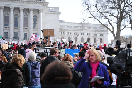 collective bargaining: Madison, Wisconsin, USA – 2-15-11 – Large crowd of protesters, wielding signs on grounds of the Wisconsin state capital, who are there to protest the bill to balance the state budget by restricting collective bargaining rights for state union employee Editorial