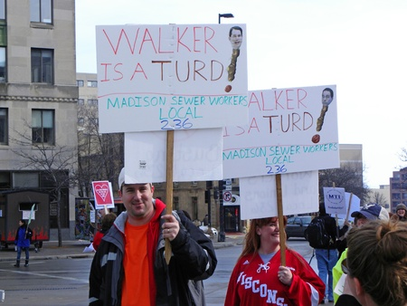 """Madison, Wisconsin, USA – 2-16-11 – Madison sewer workers with signs that say, """"Walker is a Turd� on grounds of Wisconsin state capital to protest the bill to balance the state budget."""