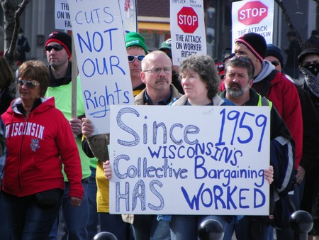 """collective bargaining: Madison, Wisconsin, USA – 2-16-11 – Protesting woman carrying sign that says, """"Since 1959 Wisconsin's Collective Bargaining Has Worked"""" on grounds of the Wisconsin state capital protesting the bill to balance the state budget."""
