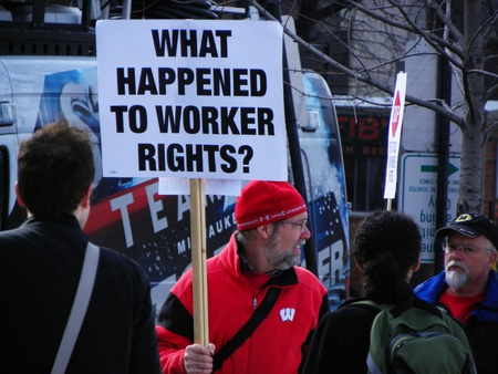 "wisconsin state: Madison, Wisconsin, USA – 2-16-11 – Protesting man carrying sign that says, ""What Happened to Worker Rights"" on grounds of the Wisconsin state capital protesting the bill to balance the state budget."