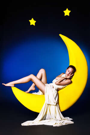 Beautiful girl in a long white dress sleeping on the moon in the night sky photo