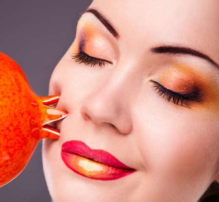 beautiful young woman with bright makeup and orange fruit photo