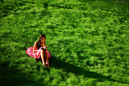 prairie: Brunette girl in red dress sitting on a green meadow and reading a book