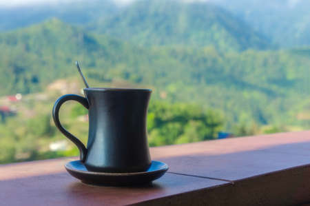 Dark cup on a saucer on a background of mountains in the clouds. Sapa, Lao Cai Province, north-west Vietnam Stok Fotoğraf