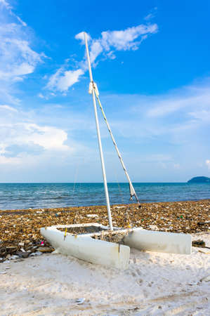 Catamaran is among the garbage. Environmental disaster. Garbage dump on Bai sao beach with white sand on the coastline. Plastic rubbish pollution in ocean.Plastic water bottles and bags thrown directly into the sea with no proper trash collection or recycling. Phu Quoc island, Vietnam