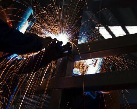 argon: Two metal workers Mig welding some steel sections.