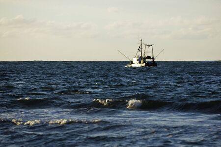 motoring: Fishing boat motoring out to sea