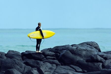 Guy standing on the waves waiting to go surfing.
