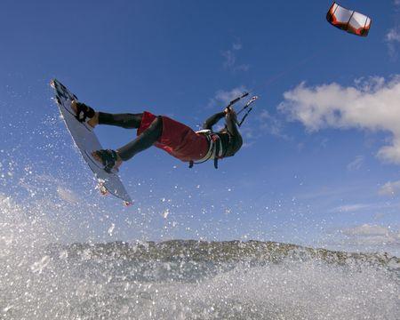 Guy voorzijde lus terwijl de vlieger surfen.