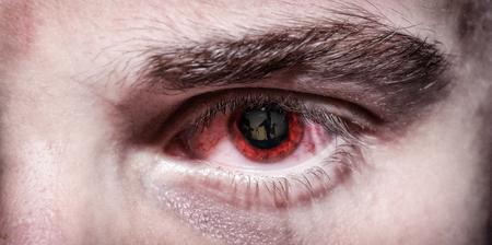 Oeil rouge du soldat épuisé avec des soldats se reflétant dans l'iris
