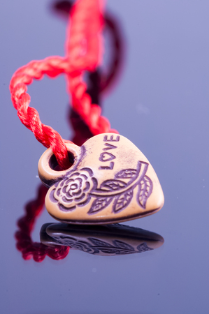Wooden heart shaped locket with red string on the bright background.