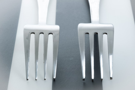 Two forks cross on striped background. 2 forks laying next to each other.