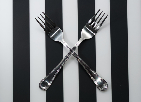 Forks. Crossed fork close-up on plate with striped background.
