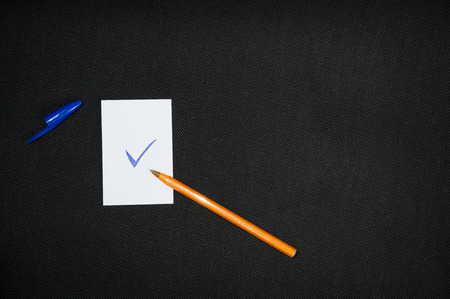 A blank sheets of paper next to a pen on a dark background. Layout for design. Top view, place for text.