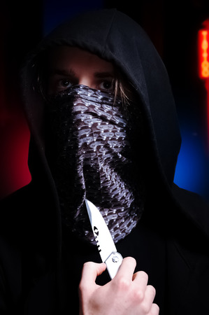 Portrait of hooded/masked man threatening with knife with police sirens and dark street in the background. Dangerous criminal. Hostile situation concept