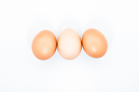 Three eggs in a row isolated on white blank background Stock Photo