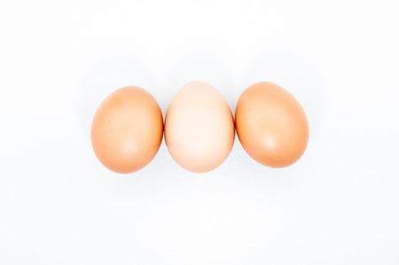 Tres huevos en una fila aislado sobre fondo blanco en blanco Foto de archivo