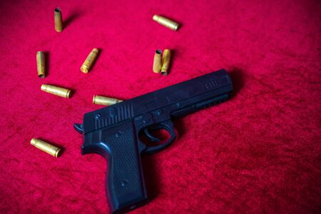 Flat lay black pistol on red velour background with golden shell casings spread around the gun