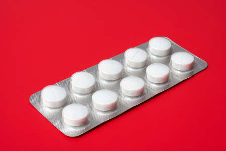 blister: blister verpakking met tabletten op een rode achtergrond