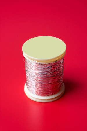 bobbin: bobbin of thread on a red background