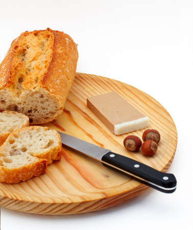 Pate, bread, hazelnuts and knife on wood plate over white background photo