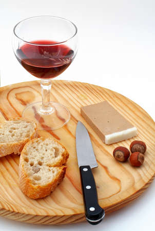 Pate, bread, glass of red wine, hazelnuts and knife a wood plate on white background photo