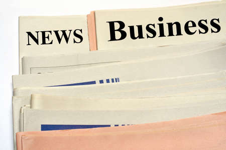 inform information: Stacked business newspapers on white background
