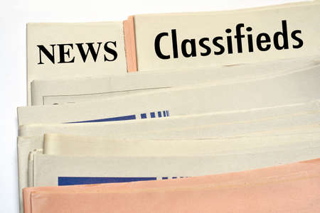 Stacked classifieds newspapers on white background photo