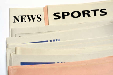 classifieds: Stacked sports newspapers on white background