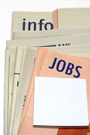 Stacked jobs newspapers on white background photo