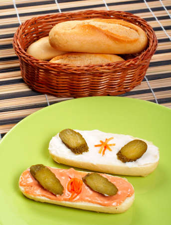 Two canapes on a green porcelain plate, and bread on a basket photo
