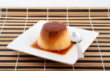 custard flavor: Close-up of a vanilla cream and caramel dessert with spoon on white dish