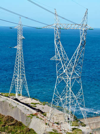 Two High voltage towers next to the sea photo