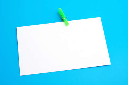 Isolated white paper with green clamp on blue background photo