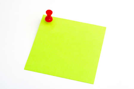 Isolated green paper with red pushnail on white background photo