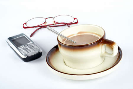 mingle: Close-up of a cup of coffee with the spoon inside, cellular phone and pair of glasses on white background