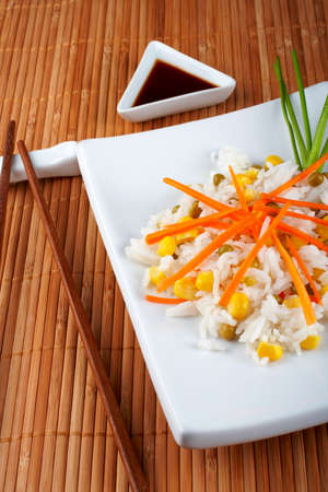 japanese cookery: Salad of rice with sauce and sticks on bamboo mat