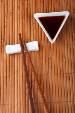 dinners: A pair of asian chopsticks and soy sauce, over the bamboo mat