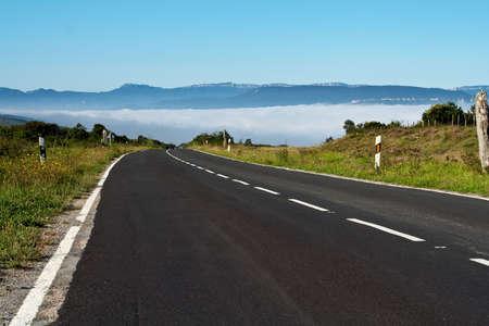 An asphalt road towards the fog photo