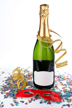 Champagne bottle with red mask, ribbons and confetti. Blank label for add text photo